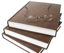 stack of research books with a pair of glasses resting on top
