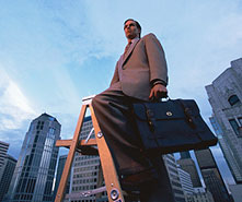 businessman standing atop ladder