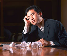businessman at desk surrounded by crumpled pieces of paper