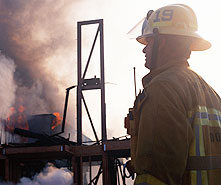 firefighter standing near industrial fire