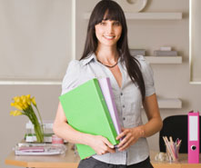 Woman holding folders and smiling.