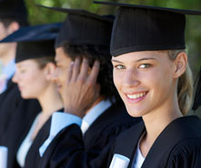 A girl in her cap and gown smiling.