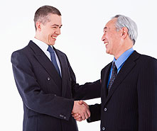 younger and older businessmen shaking hands