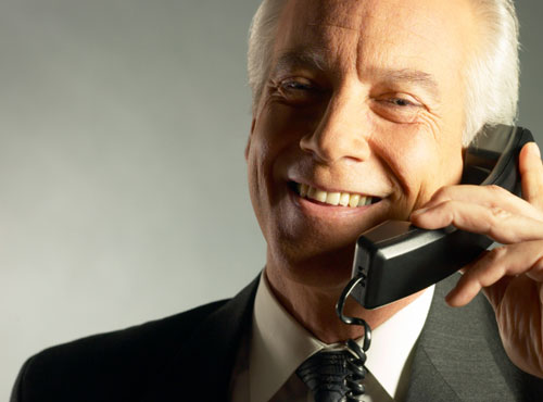 An older businessman talking on the phone.