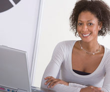 A woman working at a computer, smiling.