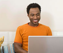 A man sitting at his computer smiling.