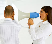 A woman yelling with a bullhorn in a man's ear.