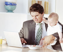 businessman working at home while holding baby